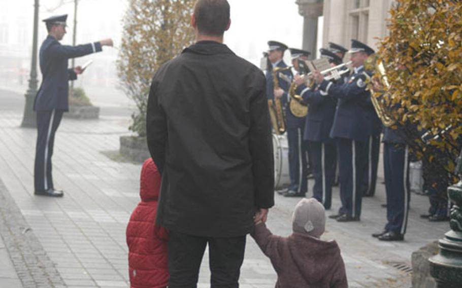 A Belgian man and his two children watch the U.S. Air Forces in Europe Band play on a foggy Veterans Day morning near the Oudenaarde, Belgium, city hall.