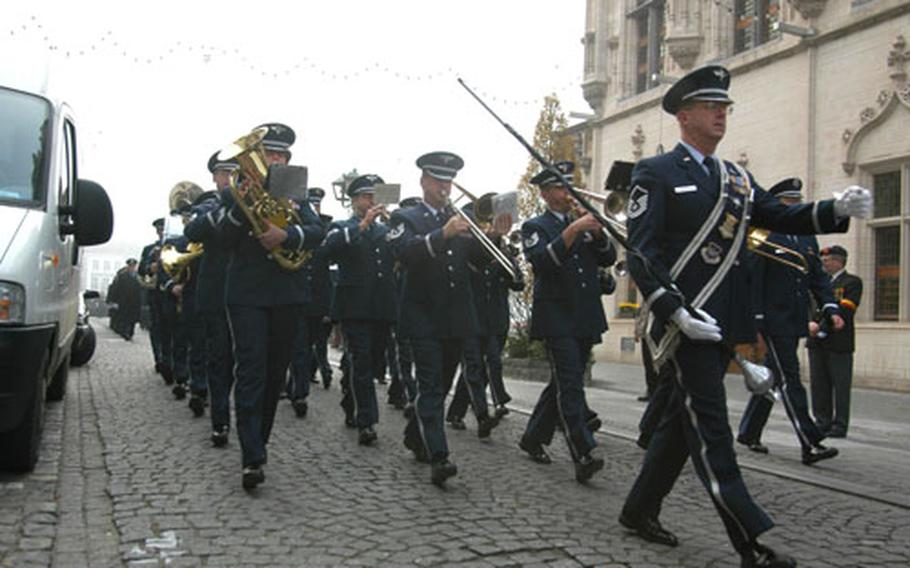 The U.S. Air Forces in Europe Band marches down a Belgian street before performing at a Veterans Day ceremony.