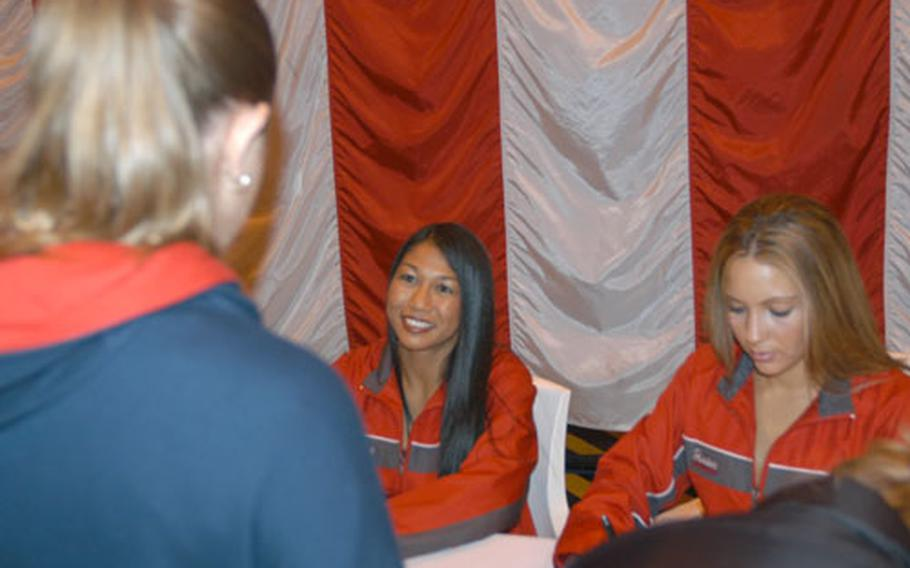New England Patriots cheerleaders Elizabeth Harlow, left, and Kristin Gauvin sign autographs and talk to members of the military community at Aviano Air Base, Italy, after performing Thursday night during the Operation Seasons Greetings entertainment series.