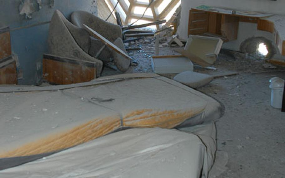 A room on the 15th floor of the Palestine Hotel in Baghdad, Iraq, damaged in rocket attacks Friday. The hole in the wall at the right is where a rocket penetrated the masonry, hurling a chair across the room and overturning a mattress.