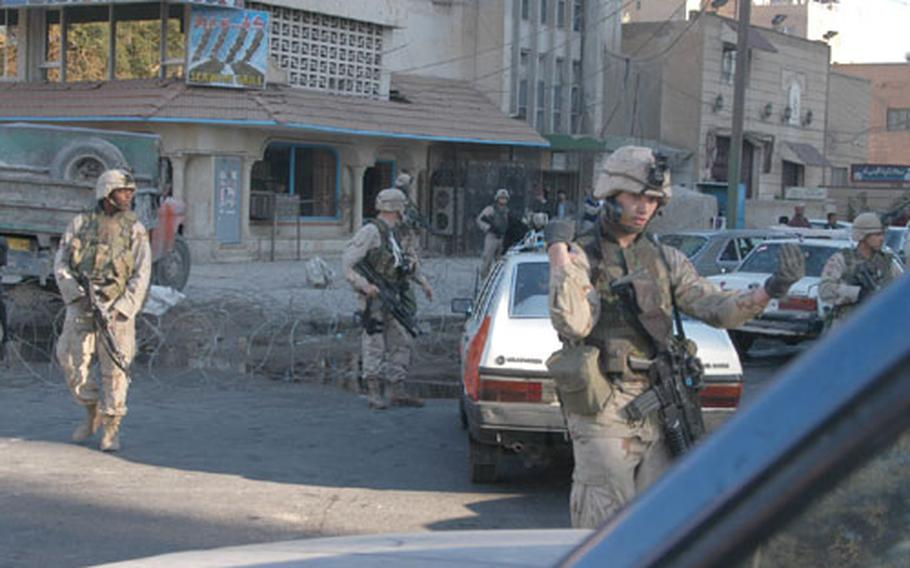Troops from the 1st Armored Division seal off a street corner in Baghdad, Iraq, Friday morning after finding a donkey cart and some unfired rockets shortly after an attack on the Palestine Hotel about a block away.