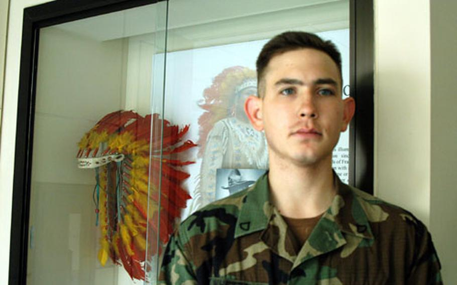 PFC Wayne Whetzel, a 2nd Infantry Division solder and member of the Shawnee tribe, stands in front of a traditional Native American headdress created by 2ID soldiers.