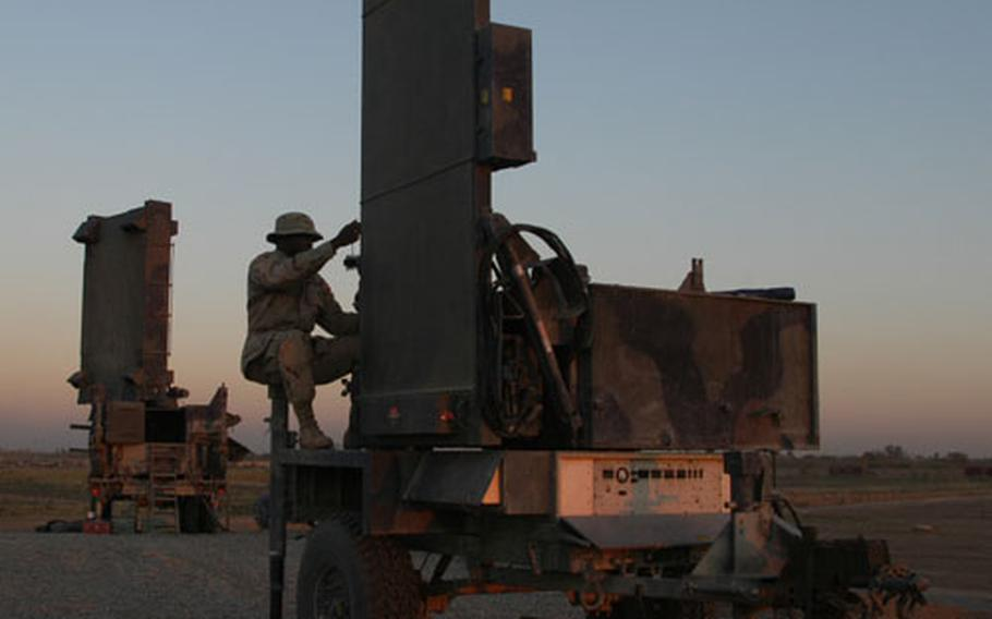 Spc. Nathaniel Rumph, a radar repairman with the 1st Armored Division, pulls maintenance on a portion of the Firefinder radar system at Baghdad International Airport in Iraq.