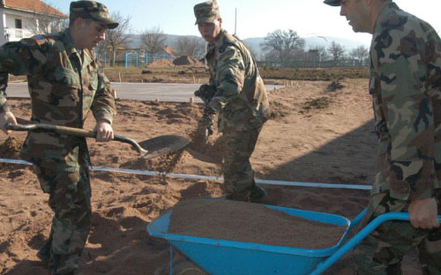 Cpl. Mike Fitzgerald of the 86th Medical Company, Air Ambulance, and Sgt. Raymond Hagen of the 682nd Engineer Battalion shovel sand into wheelbarrow held by Capt. Mike Wiedrich, of Headquarters and Headquarters Company, 34th Infantry Division. The sand was used to even out the volleyball court American and Turkish troops were building for Budozelje villagers.