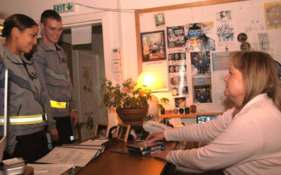 Linda Lorenzana rents out a DVD to soldiers stationed at Eagle Base, Bosnia and Herzegovina. She runs a United Services Organization center at the base where troops can watch movies, browse the Internet, read books and magazines, all in a cozy living room-like atmosphere with couches, warm lights and homemade treats. Lorenzana puts in 10- to 13-hour workdays to create a home away from home for the soldiers.