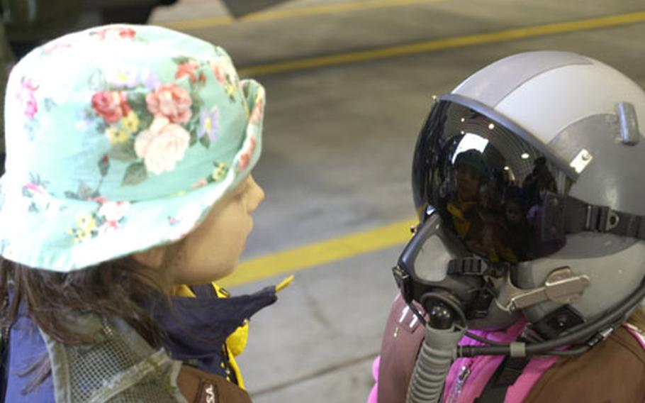 Andi Jones checks out her reflection in the visor of a flight helmet worn by another member of her Osan Air Base Brownie troop.