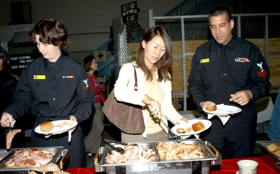 """Petty officer 3rd Class Heidi Perry, civilian employee Hiromi Toyoda and Petty Officer 2nd Class Timothy Santiago help themselves to a pre-Thanksgiving feast at the annual Naval Air Facility Misawa """"Turkey Feed."""""""