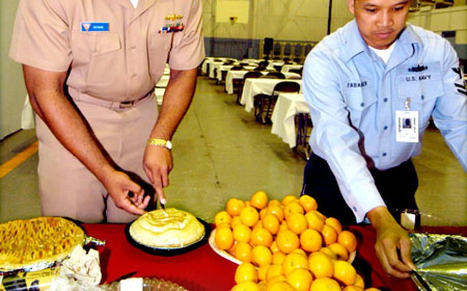 """Lt. Phillip Deboe and Petty Officer 2nd Class Jerry Fababier serve traditional Thanksgiving goodies at the annual """"Turkey Feed."""""""