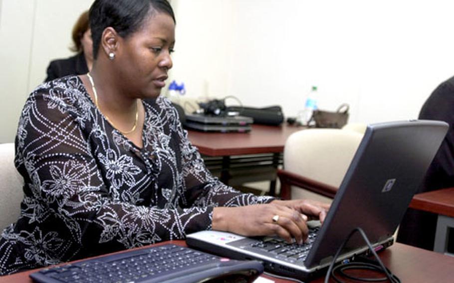 Karen Gordon, a third-grade teacher at Sollars Elementary School on Misawa Air Base, Japan, downloads a math flash-card game from her laptop onto her AlphaSmart Dana computer.