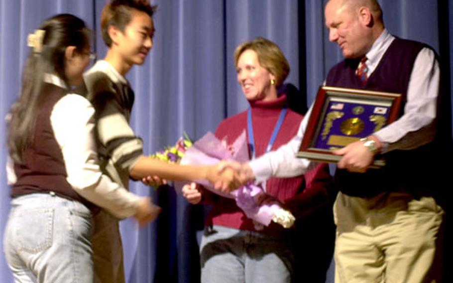 Korea schools superintendent Bruce W. Jeter and his wife, Linda, accept a plaque Monday during an honors assembly at Seoul American High School. Jeter will leave Korea Dec. 20; his replacement has not been named.