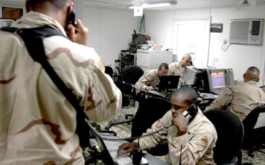 Soldiers of the 1st Armored Division's artillery brigade in Baghdad, Iraq, work their computers and radios seconds after the brigade's Firefinder radar detected the firing of what could have been an insurgent mortar round. The soldiers are on duty in the artillery tactical operations center at Baghdad International Airport.