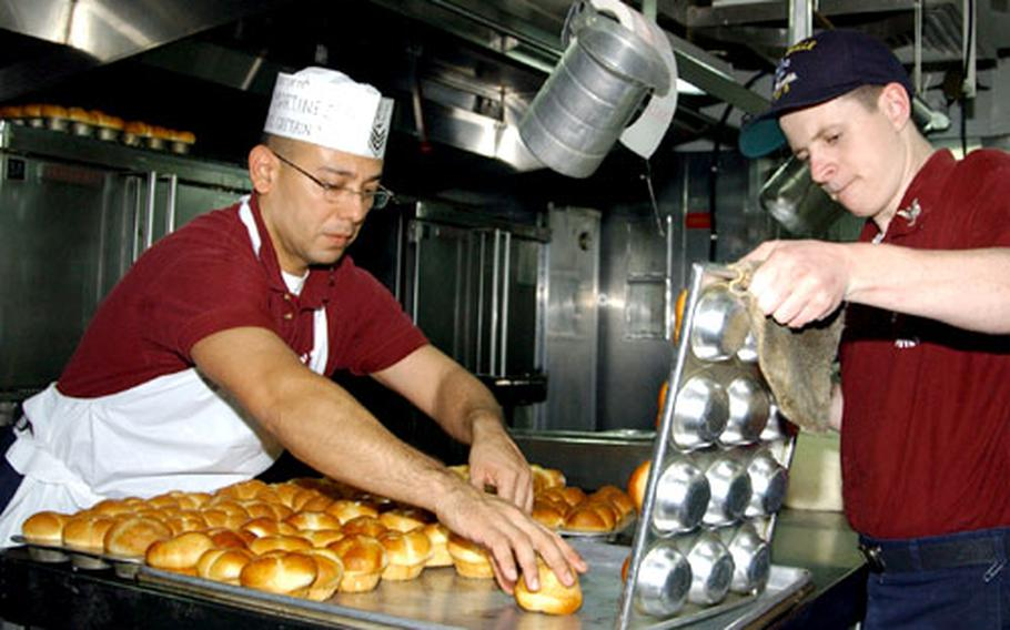 Petty Officer 1st Class Luis R. Martinez, left, and Petty Officer 3rd Class Mike Mears arrange cloverleaf rolls Wednesday in preparation for Thanksgiving dinner on the USS La Salle in Gaeta, Italy.