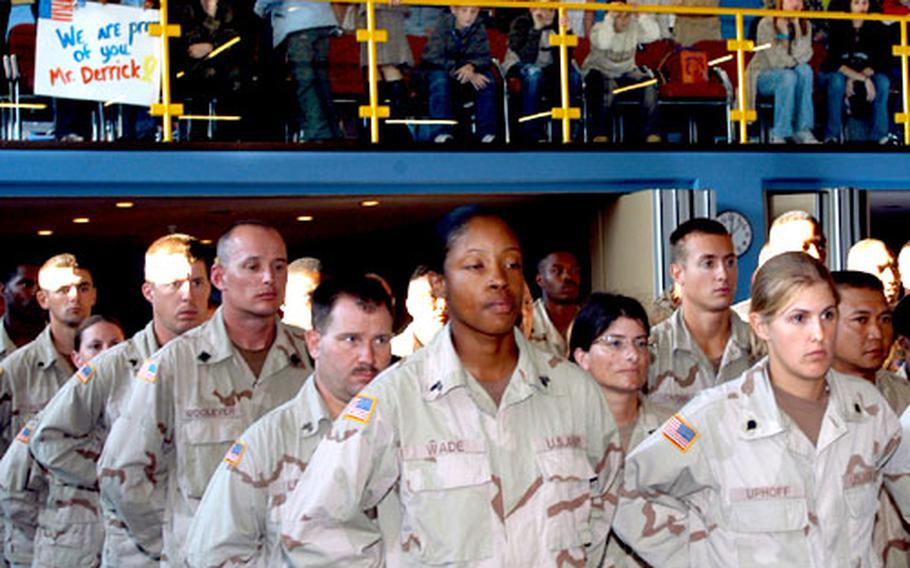 Members of the 77th Maintenance Company stand in formation after returning to Babenhausen, Germany, from a nine- month deployment to Iraq, as family members and friends wait impatiently on the balcony behind them.