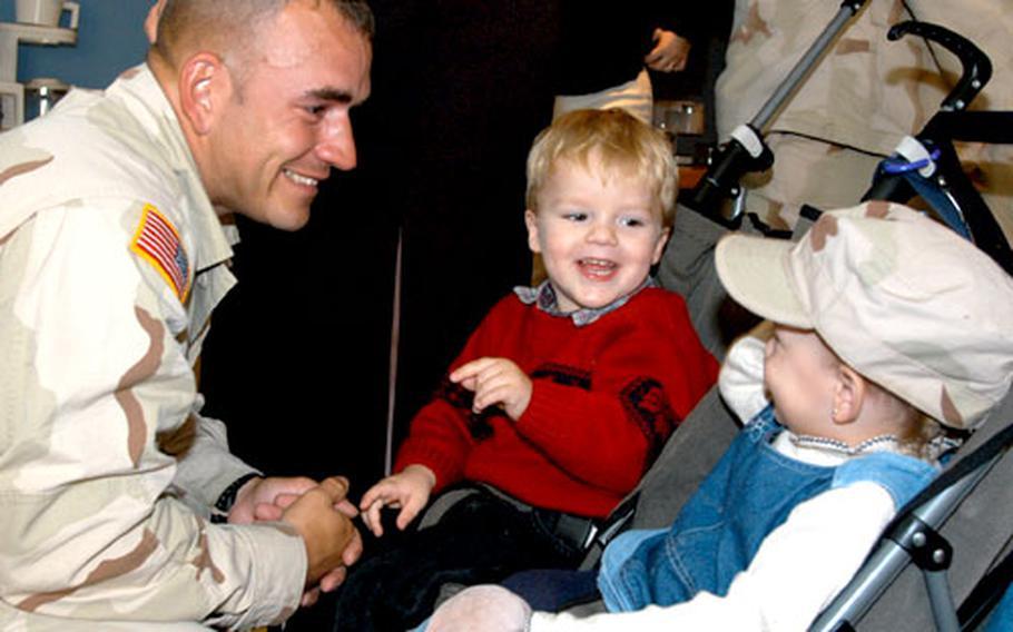 Sgt. Darrick Blackburn gets a laugh as daughter Corrina, 1, tries on his hat as son Garrett, 3, watches.