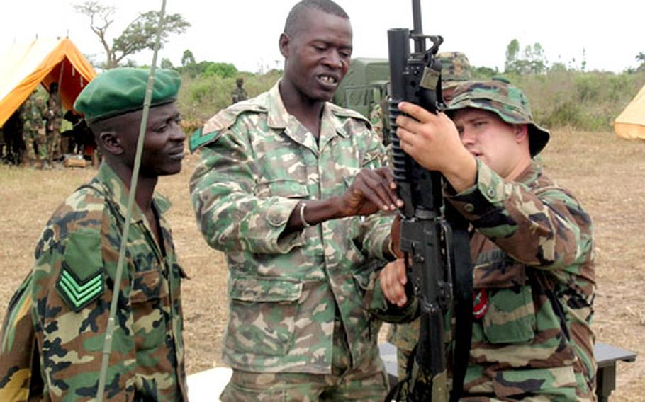 A U.S. Marine demonstrates an assault rifle to members of the Gambia military. The training session was part of the 2004 West African Training Cruise.