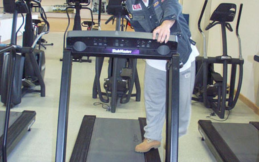 Sgt. Omar Castro of the 4th Battalion, 3rd Air Defense Artillery, makes adjustments to a treadmill at the Army's Larson Barracks in Kitzingen, Germany. The Larson gym reopened Wednesday after a yearlong, $2 million makeover.