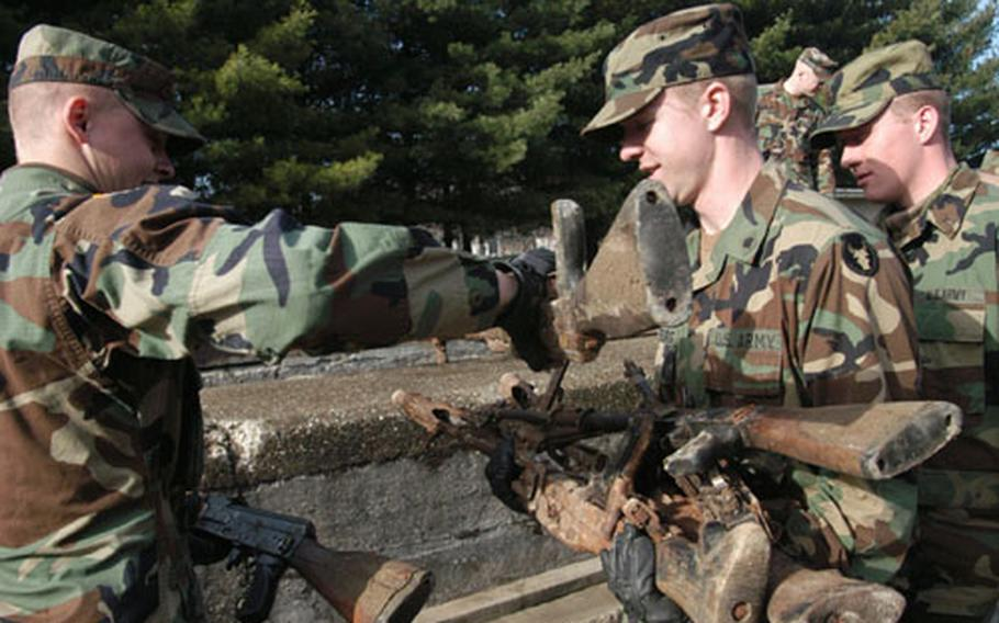 American soldiers collect the crushed weapons from the line so they could lay down more to be crushed by a tank. The crushing on Tuesday marked the end of a successful three-day weapons turn-in campaign in three communities in northeastern Bosnia during which local police and military joined the American troops.
