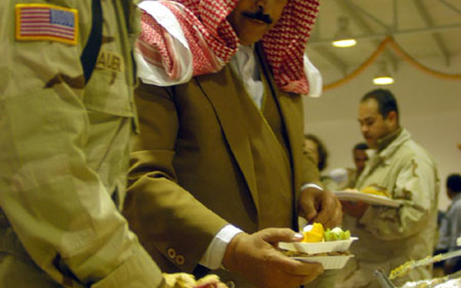 Second Lt. Jeremy Sauer, 23, a Black Hawk pilot from Boise with the 6th Battalion, 101st Aviation Brigade, 101st Airborne Division, and Maj. Gen. Sheik Abdul Razak, member of the Mosul City Council, dig into pie at the new chow hall at Qayyarah West Airfield in northern Iraq on Thursday. Local Iraqis officials were invited to the Thanksgiving celebration.