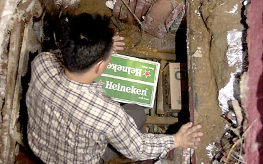 A South Korean customs agent stands in a tunnel that smugglers used to move 62,000 cases of wine and beer from a Hannam Village storage container to a fake storefront off-base. The two-year scam netted two men nearly $2 million.
