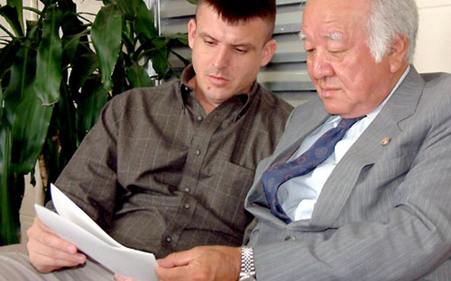 Marine Maj. Michael Brown and his attorney, Toshimitsu Takaesu, read a letter Brown presented to the U.S. Consulate on Okinawa requesting assistance from Ambassador Howard Baker concerning his ongoing trial on a charge of attempted rape. Brown was indicted Dec. 19, 2002; his trial is to resume Jan. 15.