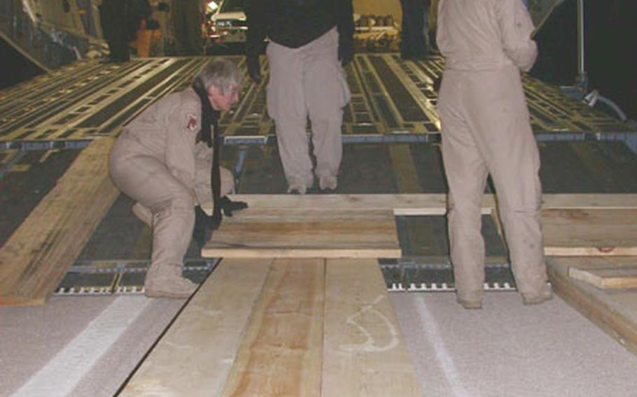 Master Sgt. Eve Irwin, left, and Senior Airman Laura Tumlinson, right, Air Force reservists from the 300th Airlift Squadron at Charleston Air Force Base, S.C., work with Federal Emergency Management Agency members to construct a wooden ramp at the back of a U.S. Air Force C-17 Globemaster III Monday at Kerman International Airport, Iran. The ramp was used to unload humanitarian relief supplies for earthquake victims.
