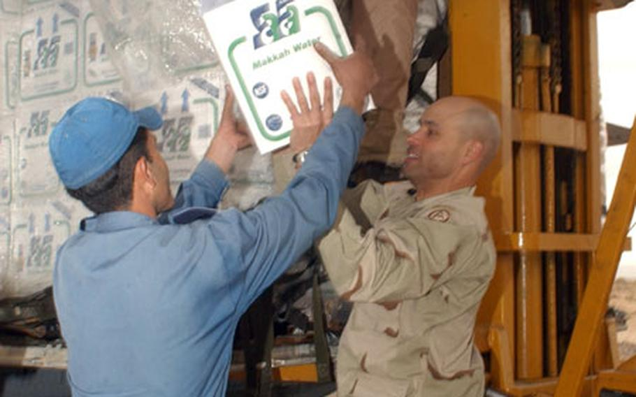 Lt. Col. Vic Harris, Coalition Forces Land Component Command public affairs officer and an Iranian servicemember unload medical supplies and water from a U.S. Air Force C-130 in Kerman, Iran.