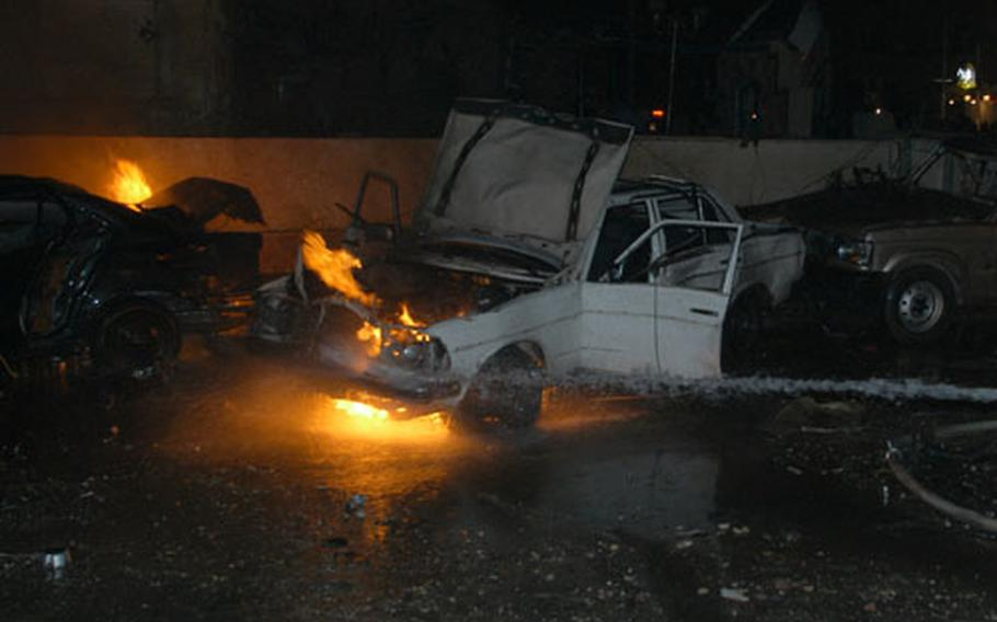 Cars burn outside a restaurant in Baghdad, Iraq, on New Year's Eve after a powerful car bomb went off, killing five patrons and injuring more than 30 other people. The blast brought troops of 1st Armored Division to the scene.