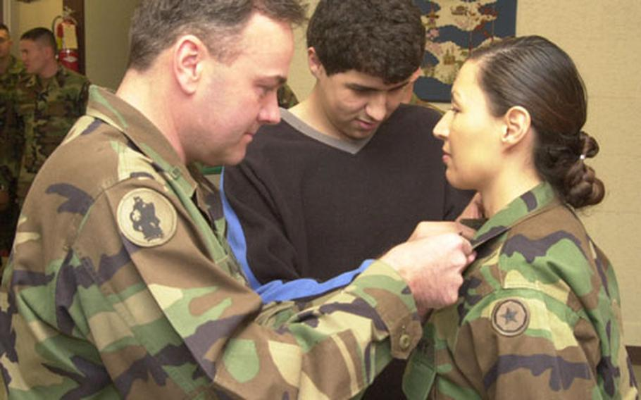To start out the new year, husband and newly promoted Chief Warrant Officer Jay Walker and son, Matt Michael (center) pin on Master Sgt. Julianna Walker's new collar device at a promotion ceremony at Sagami Depot Wednesday. Both Chief Warrant Officer Walker and Master Sgt. Walker were promoted on the same day.