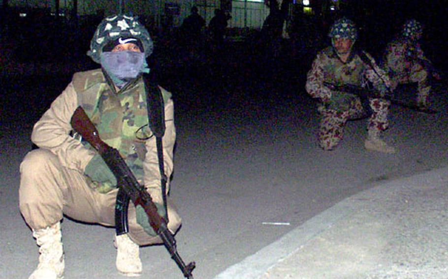 Members of the Iraqi Civil Defense Corps crouch during a raid on Monday.