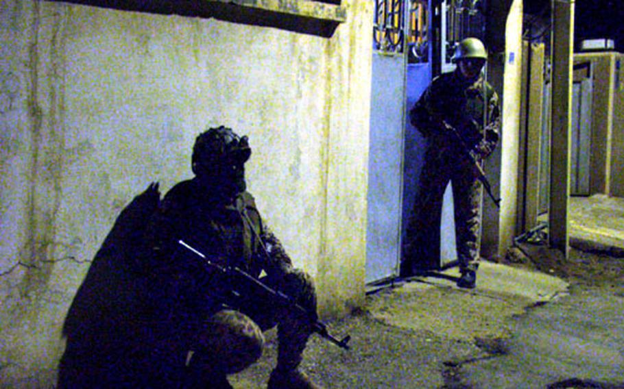 Iraqi defense corps troops wait before entering a home during a hunt for a terror suspect.