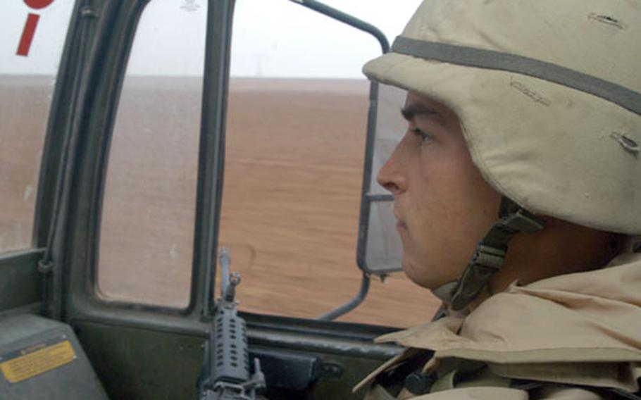 With nothing but vast open desert surrounding him, Pfc. Greg Schlaht, 20, from Aberdeen, Wash., pulls security from the passenger seat of a a 2½-ton truck during a four-hour trip to remote bases near Qayyarah Air Field in northern Iraq. Schlaht is an ammunition specialist for the 2nd Battalion, 320th Field Artillery Regiment of the 1st Brigade, 101st Airborne Division.