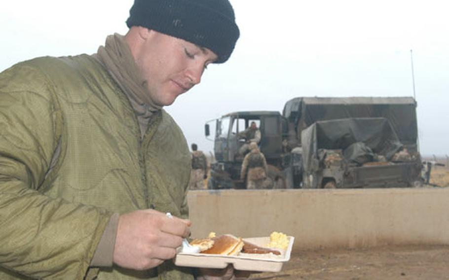 Pfc. Jeremy Davidson, 21, from Cheyenne, Wyo., enjoys some hot breakfast at the remote Objective Wolf camp, from which he guards the Iraq-Turkey pipeline.