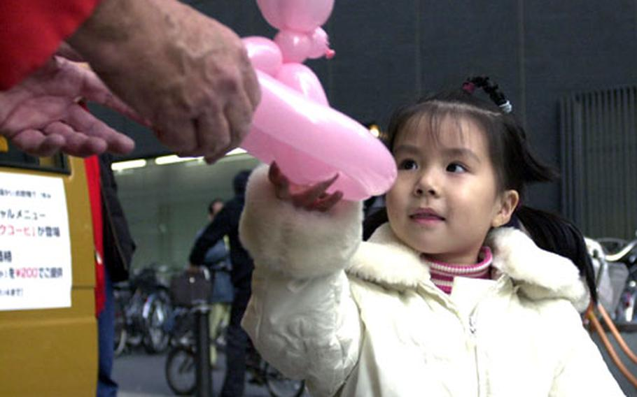 A child reaches out for a balloon bunny in Ikebukuro.