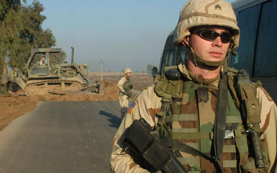 Sgt. Joshua Smith, foreground, a reservist from Joplin, Mo., stops traffic along Iraqi Highway 1, also known as Main Supply Route Tampa, as fellow engineers drag brush across the highway.