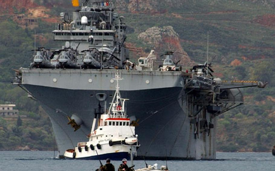 The USS Wasp pulls into Souda Bay, Crete, in March 2002 as members of the base's port security unit sail nearby. Souda Bay was recently awarded the Secretary of the Navy's Meritorious Unit Commendation for its role in operations between Sept. 11, 2001, and Sept. 30, 2002.