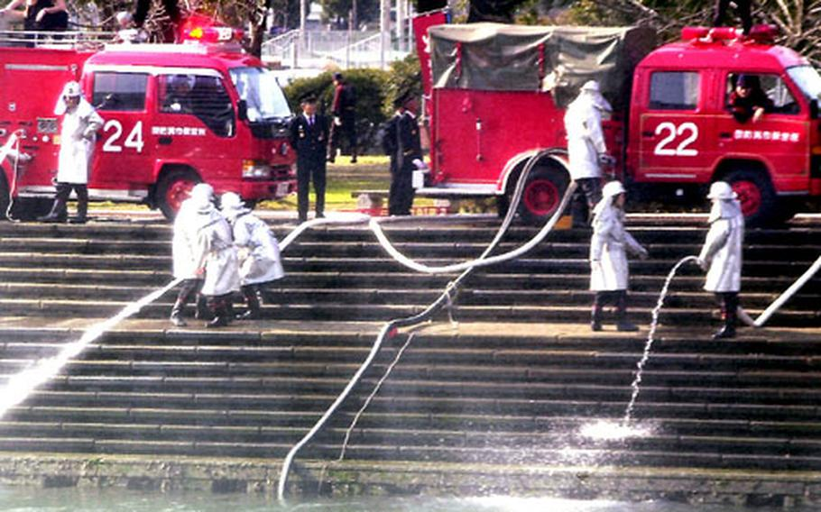 Personnel from a Sasebo city fire detachment hold a hose nozzle steady as a powerful flow of water comes to an end in the canal.
