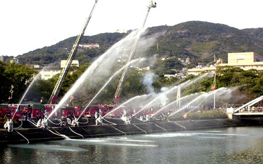 Fire engines from about 30 Sasebo City Fire Department detachments on Tuesday gathered near the Albuquerque Bridge in Sasebo, Japan, while personnel from each unit aimed hose nozzles firing streams of water, creating massive arches streaming through the air and falling into the canal that flows under the bridge.
