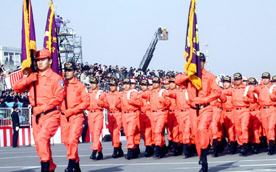 Rescue squadrons from Tokyo's Metropolitan Fire Department parade at the Dezomeshiki.