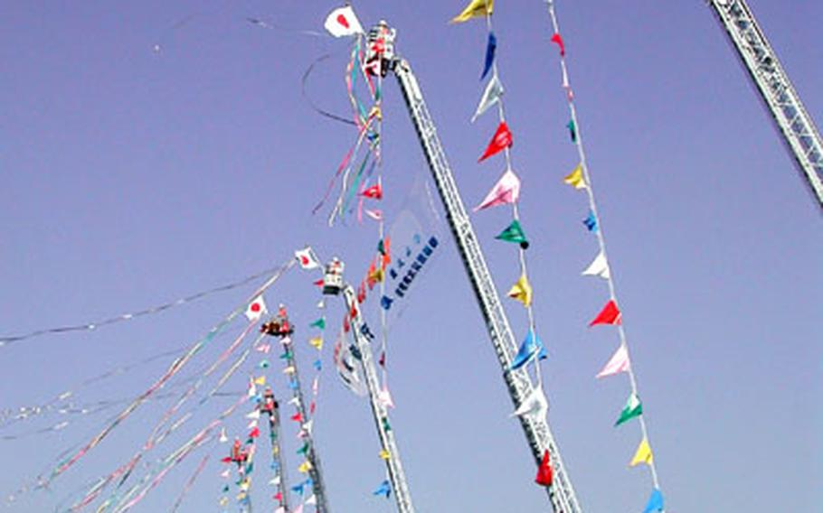 Ladder trucks drop colored streamers at the closing ceremony of the review at Ariake.