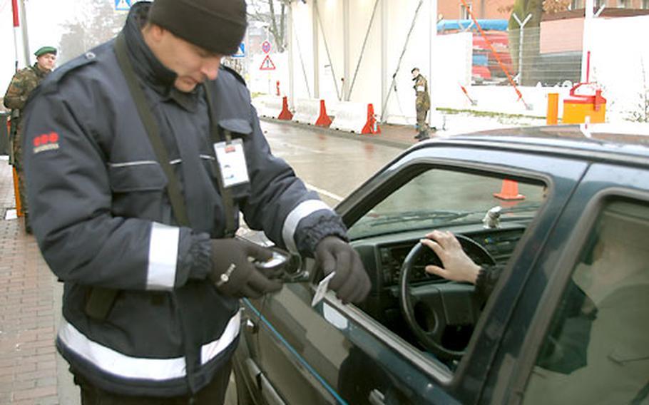 Stefan Zellner, Securitas gate guard in Bamberg, Germany, scans an identification card Wednesday at Warner Barracks' Gate 3.