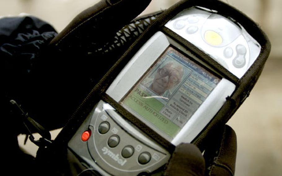 Stefan Zellner, Securitas gate guard in Bamberg, shows the display information after an identification card is scanned Wednesday at Warner Barracks.