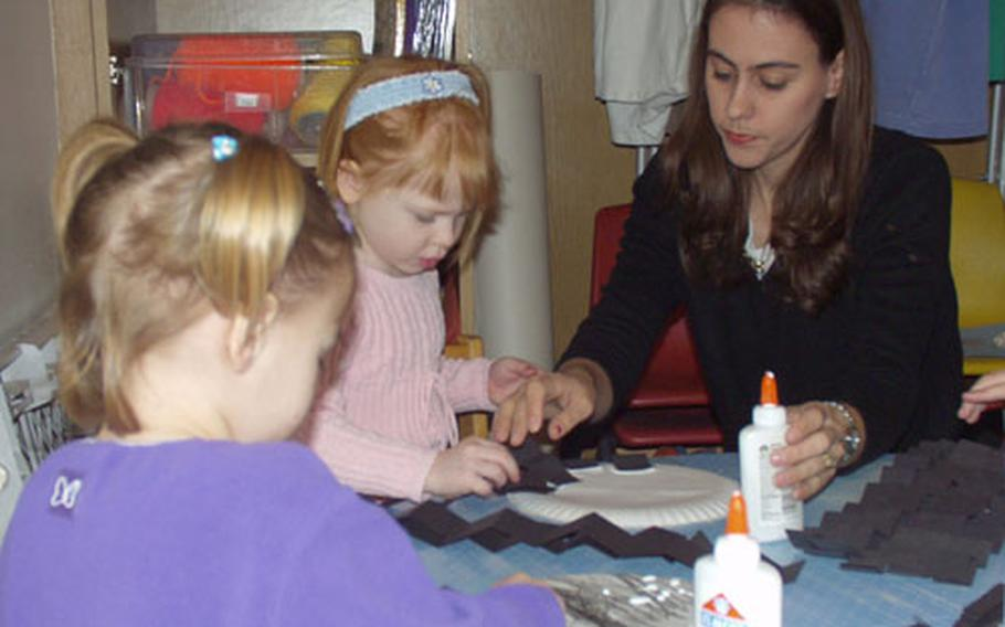 Angela Hamilton, a teacher with the Time for Tots program on Rhein-Main Air Base, Germany, helps children make paper spiders out of construction paper and paper plates.