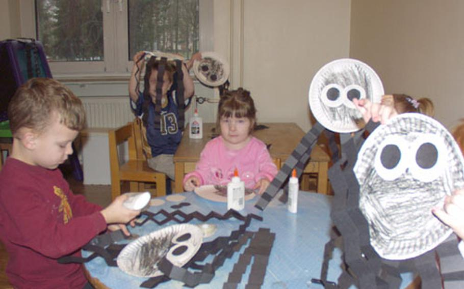 Children at the Time for Tots program on Rhein-Main Air Base, Germany, show off their spiders made from construction paper and paper plates. The Time for Tots program helped the Rhein-Main community win the best Family Support Center award for 2003.