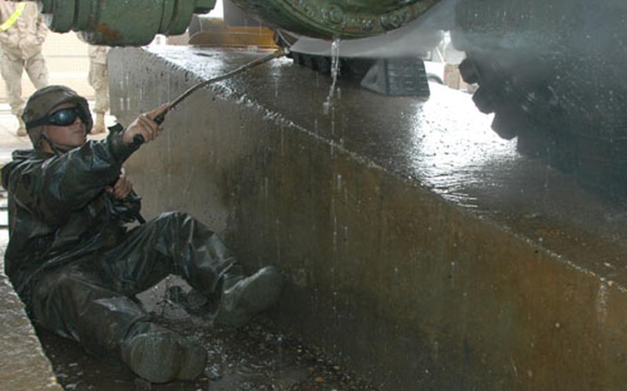 Pfc. Clinton Miskove, 20, of Palm Harbor, Fla., sprays the underside of his wrecker last week at Camp Doha, Kuwait.