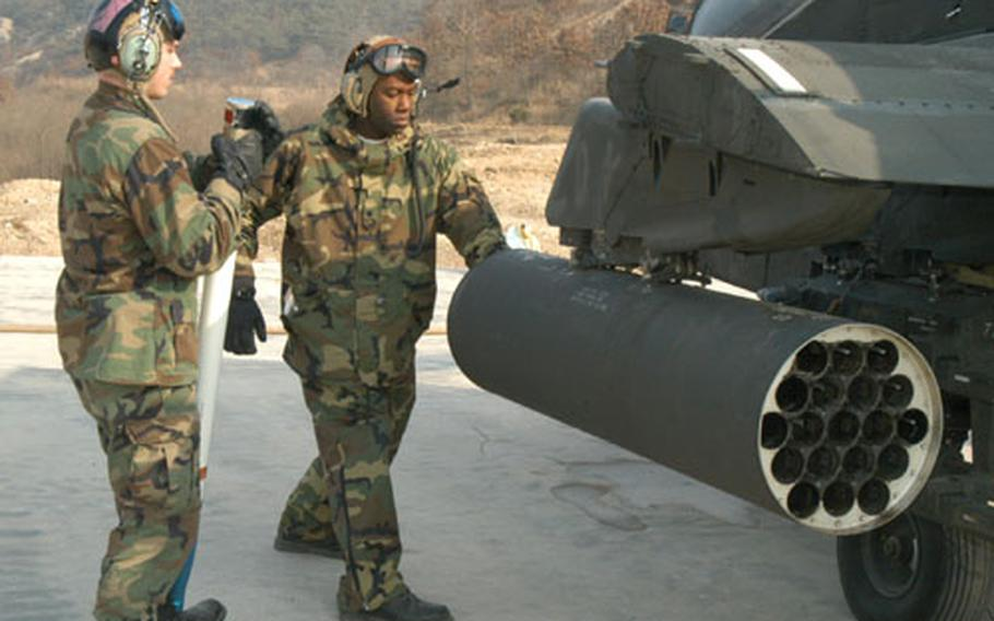 Ground crew members from the 1st Battalion, 2nd Aviation Regiment load Hydra rockets into an Apache before gunnery practice at Rodriguez Range this week.
