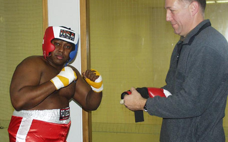Army Master Sgt. Sam R. Tidwell, left, warms up with a trainer Saturday for a fight night on Patch Barracks in Stuttgart.