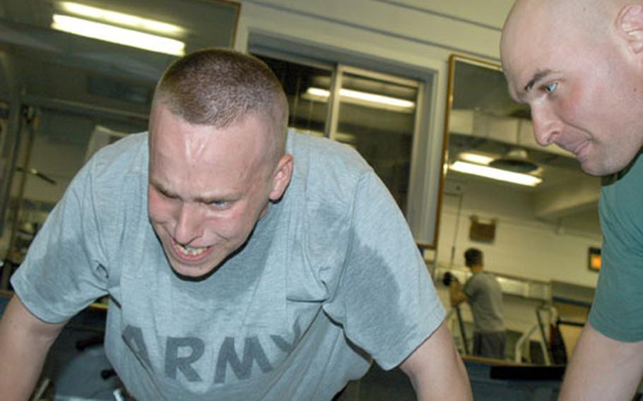 Pfc. Chris Robb shows the strain as he does push-ups under the watchful eye of Staff Sgt. Bryan Baker at the Camp Red Cloud gym.