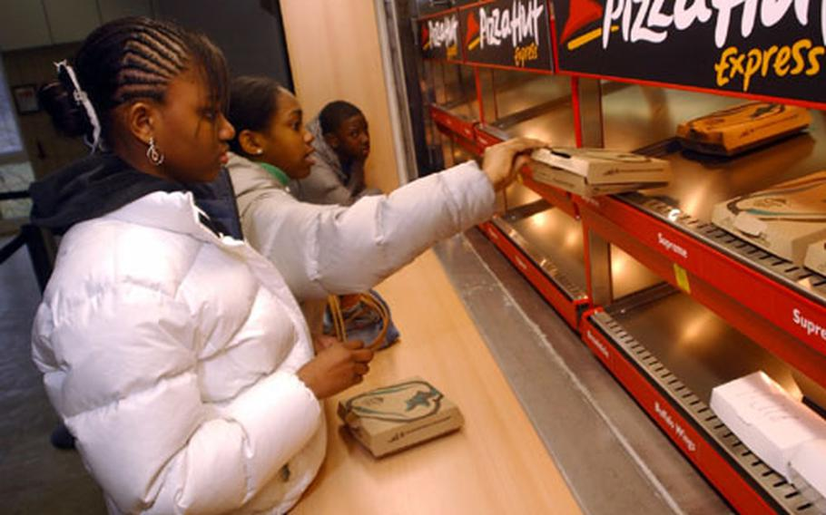 Youngsters from Wiesbaden American Middle School grab some personal pan pizzas from Pizza Hut in Wiesbaden, Germany, on Tuesday.