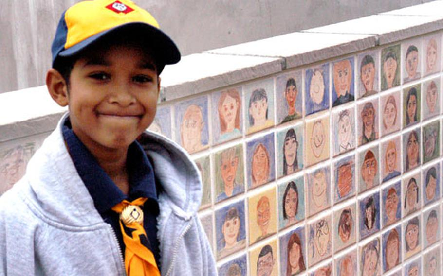 Cub Scout Christian Milton, 8, stands in front of the wall that features the likenesses of more than 500 teachers and students from the school's inaugural year.