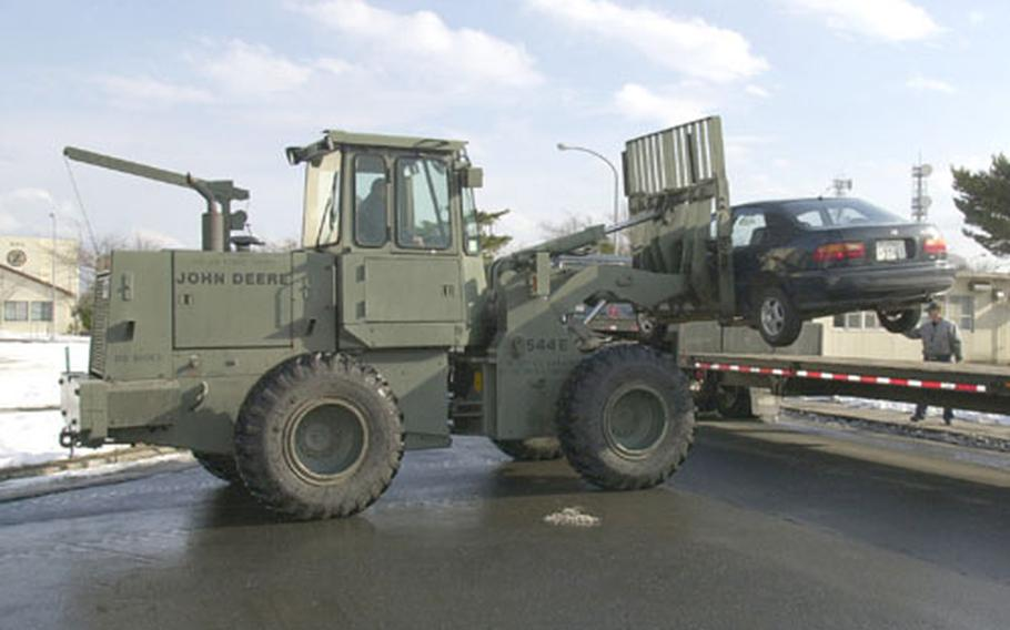 A car is fork-lifted onto a flat-bed truck to make room for snow plows to remove snow from a nearby dormitory parking lot.
